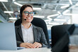 A happy female support operator is sitting at a desk and answering calls. Beautiful smiling woman talking to customers on a headset. Office employee in headphones.