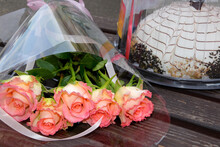 A Bouquet Of Five Pink Roses Lies On A Wooden Bench, And Next To The Cake.
