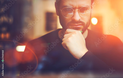 Fototapeta Cropped close up image of pensive bearded entrepreneur in optical spectacles for better views dressed in black sweatshirt.Pondering businessman in trendy eyeglasses thinking on blurred background obraz