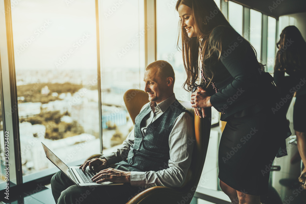 Fototapeta A business talk of two partners on the top floor of a luxurious office skyscraper in the meeting room: a cheerful man entrepreneur with a laptop and his female colleague are looking at netbook screen