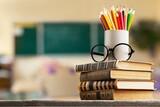 Fototapeta Kawa jest smaczna - Stack of vintage books and colorful pencils on the desk