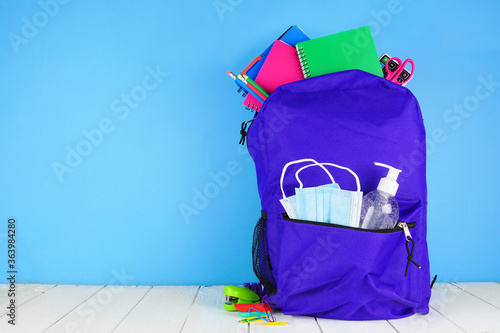 Fototapeta Backpack full of school supplies and COVID 19 prevention supplies. Blue background. Back to school during pandemic concept. obraz