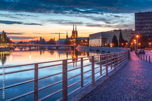 Evening on the boulevards on the Oder river in Wrocław. Illuminated historic buildings and bridges. Beautiful sky, light reflections on blurred water. Two cathedral towers in the distance