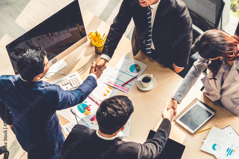 Fototapeta Group business people handshake at meeting table in office together with confident shot from top view . Young businessman and businesswoman workers express agreement of investment deal.