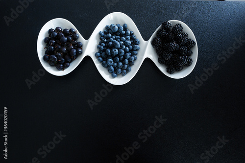 Photo Set of different types of black berries in a white plate on a black table
