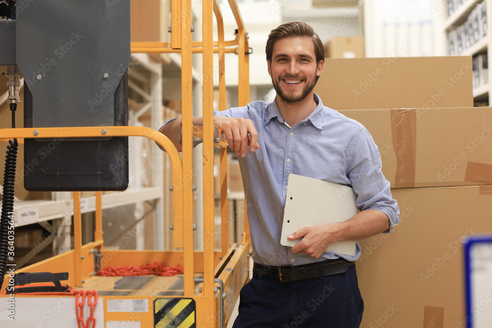 Fototapeta portrait of a smiling young warehouse worker working in a cash and carry wholesale store.