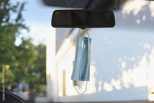 Obraz na plátně Surgical mask hanging from the mirror inside the car