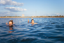 Two Girls Resting On The Dead Sea. Two Girlfriends Swimming In A Salt Lake. Women With A Beautiful Figure Floating In The Water.