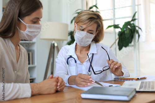 Fototapeta Middle aged female doctor therapist in medical mask on consultation with patient in office. obraz
