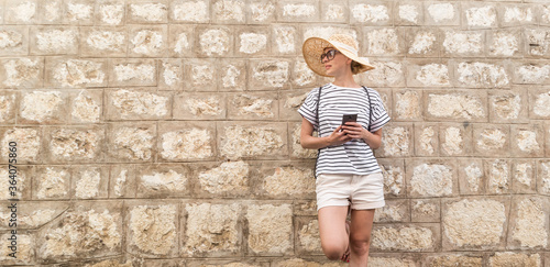 Beautiful young female tourist woman standing in front of old textured stone wall at old Mediterranean town, smiling, holding, smart phone to network on vacationes. Copy space.