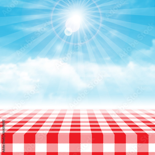 Fototapeta Gingham picnic table against blue cloudy sky obraz