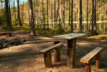 Horizontal Shot Of Wooden Table, Two Benches And Campfire On Clearing In Forest With Lake And Tall Fir Trees In Background. Vacations, Wilderness, Nature And Summertime Concept. No People Around
