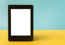 A Modern Black Electronic Book With A White Blank Empty Screen On Yellow And Blue Background With Empty Space