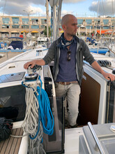 A Skipper Stands On A Yacht Be...