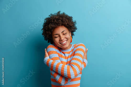 Happy woman with positive self esteem, hugs herself and holds shoulders, expresses self love and egoism, feels pleased and comfortable, closes eyes and smiles with white teeth, wears soft jumper