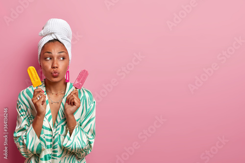 Fototapeta Photo of good looking young woman with dark skin, rounds lips and looks away, poses with ice cream, enjoys summer time, eats junk food at home, dressed casually. Housewife holds frozen dessert obraz