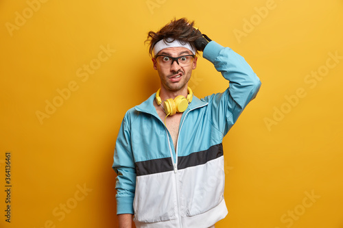 Fotografie, Obraz Waist up shot of athlete man scratches head and looks puzzled, practices sport a