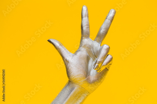 Vászonkép Elegant female hand with a silver paint on it shows three  fingers, isolated on a yellow background