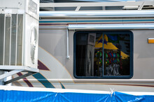 Window Of An RV Near A Fairground Midway, With Plush Game Prizes Reflected In The Window.