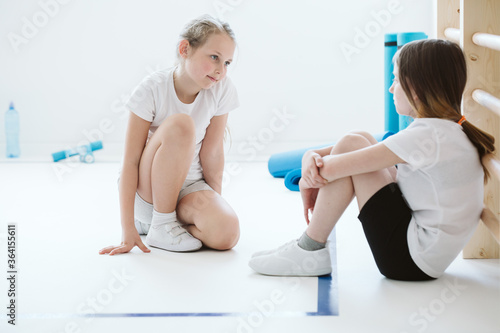 Foto Two girls sitting together at the floor of school gym before match