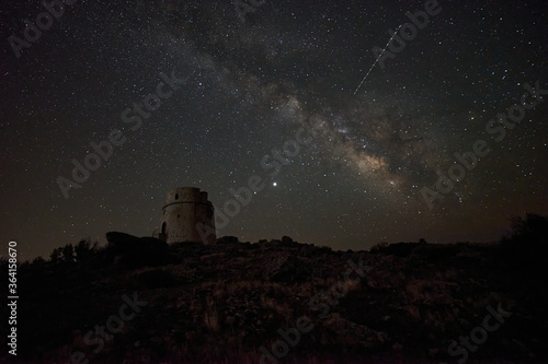 Fototapeta Milky way over an old watchtower