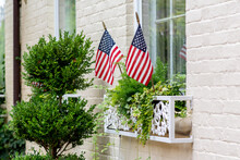 Old Colonial Style Home With White Painted Bricks Is Adorned With American Flags For The Fourth Of July (Independence Day). Trees And Green Plants On The Window Planters.