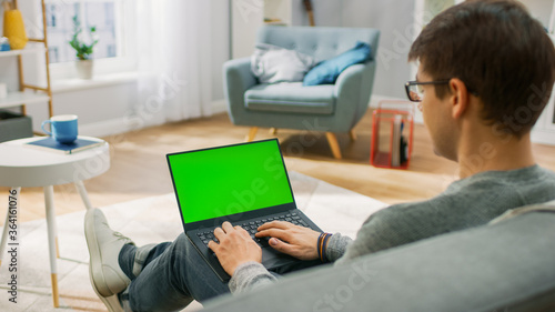 Young Man at Home Works on a Laptop Computer with Green Mock-up Screen. He's Sitting On a Couch in His Cozy Living Room. Over the Shoulder Shot.