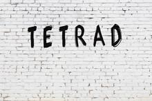 Inscription Tetrad Painted On White Brick Wall