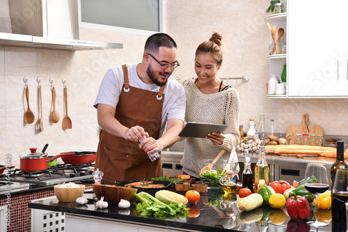 Obraz Loving young Asian couple using digital tablet and cooking in kitchen making healthy food together feeling fun - fototapety do salonu