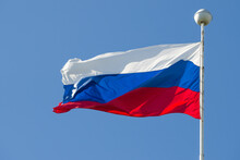 Russian Flag On A Flagpole Against A Blue Cloudless Sky
