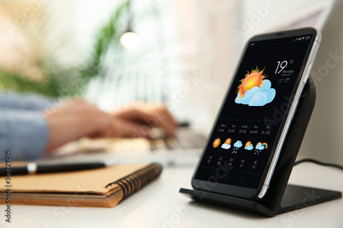 Fotografía Smartphone with open weather forecast app on white table indoors