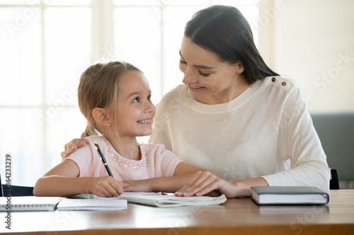 Smiling mother and adorable little daughter studying at home together, pretty preschool girl writing with pen, sitting at work desk, caring mum helping with school homework, homeschooling