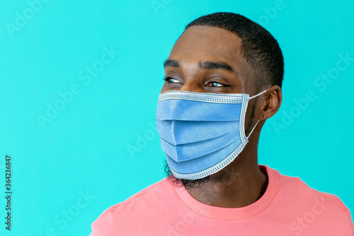 Portrait of a young african man wearing mask for coronavirus looking to side, ag Canvas Print