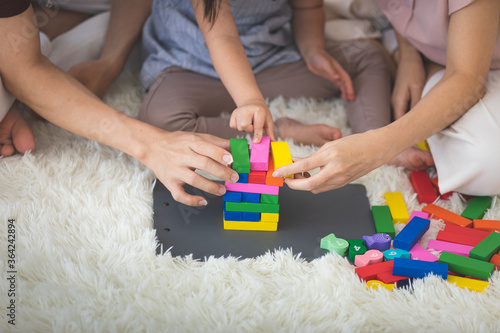 Little girl with learning disabilities Or the group of dow syndrome is learning about colorful wood toy with family teaching and encouraging beside. Education special concept.