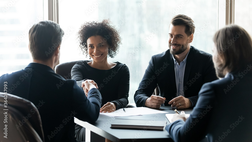Fototapeta Happy multiracial partners establishing partnership, shaking hands at negotiations meeting. Confident businessman shaking hands with smiling african american female professional, thanking for help.