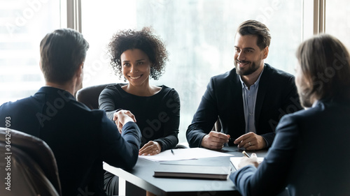 Fototapeta Happy multiracial partners establishing partnership, shaking hands at negotiations meeting. Confident businessman shaking hands with smiling african american female professional, thanking for help. obraz
