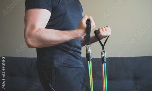 Fotografia Man doing exercises with resistance bands at home.