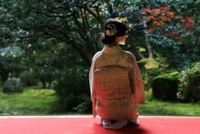 Japanese Woman In Kimono Sitting In Front Of A Japanese Garden