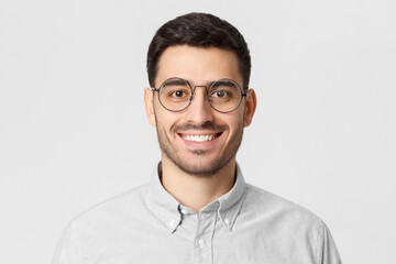 Close-up portrait of young smiling handsome man, feeling confident as professional, isolated on gray background