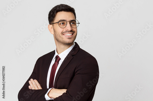 Obraz Young successful smiling businessman or CEO, cheif executive officer with crossed arms looking away, isolated on gray background - fototapety do salonu