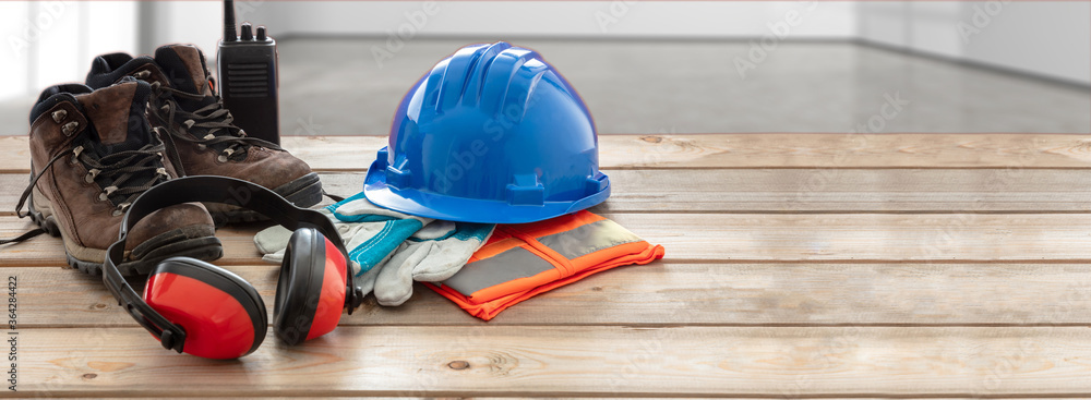 Fototapeta Work safety protection equipment. Industrial protective gear on wooden table, blur site background.