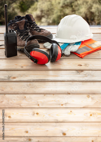 Work safety protection equipment. Industrial protective gear on wooden table, blur construction site background.