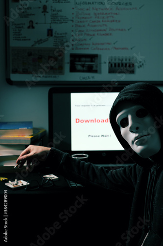 Persona adulta anónima sentada, fumando y esperando una descarga de información en su computador Canvas Print