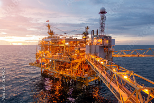 Offshore oil and gas rig platform with beautiful sky in sunset time for business industry concept