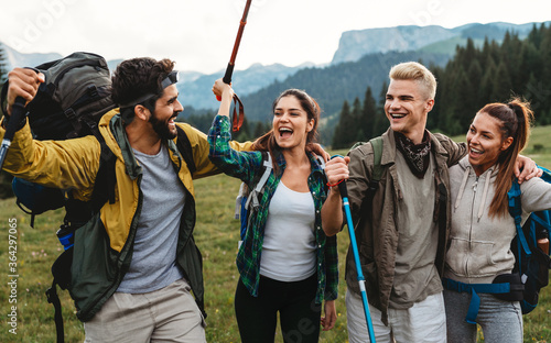 Fototapeta Group of happy fit friends hiking, trekking together outdoor nature obraz