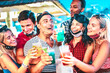 Happy multiethnic people drinking at night bar with open face masks - New normal summer concept with millenial friends having fun together - Focus on middle guy and girl with defocused background