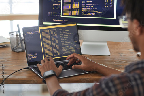 Back view at African-American IT developer typing on keyboard with black and orange programming code on computer screen and laptop, copy space