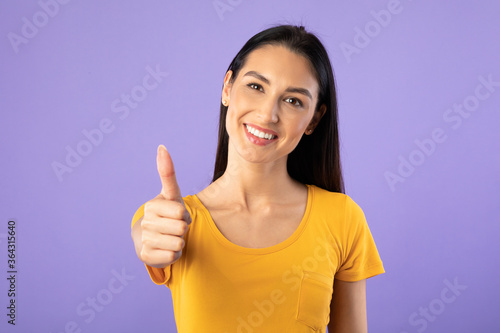 Valokuvatapetti Young woman showing thumb up and smiling
