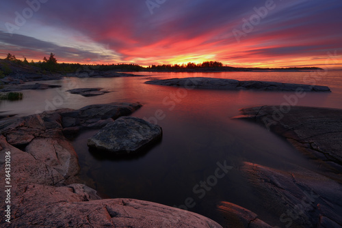 Rocky shore of the orthern lake at dawn, lake Ladoga Wallpaper Mural