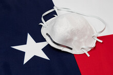 Texas State Flag And N95 Face Mask. Concept Of State And Local Government Face Covering Mandate, Order, Requirement And Social Distancing During Covid-19 Coronavirus Pandemic
